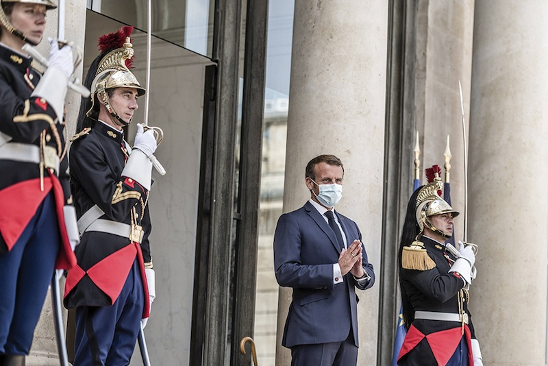 Sens du décor : les gardes républicains n'ont pas droit au masque, le Président en arbore un.