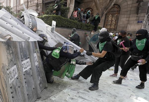 Des antifas féministes essayent de franchir un barrage de policières à Mexico pendant une manifestation en faveur de l'avortement.