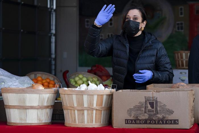 Kamala Harris salue les légumes sur un marché.